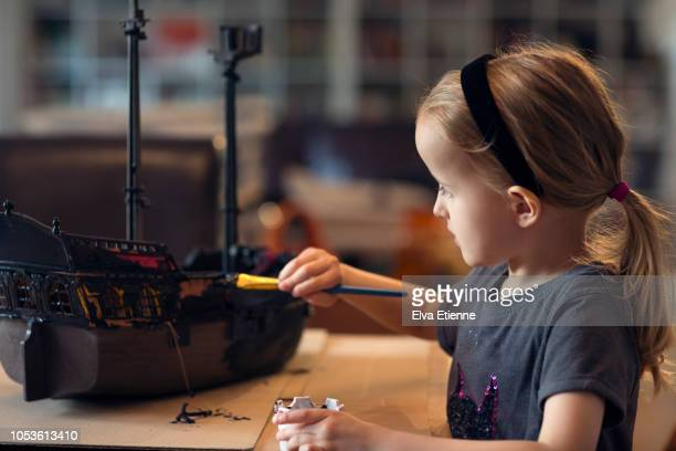 Child painting a toy pirate ship black