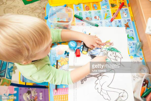 Child painting in coloring book