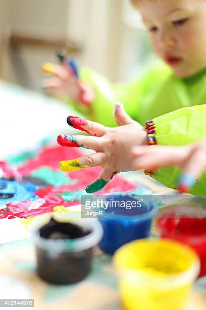 Kind Malen mit bunten Fingerpaint