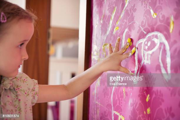 Child painting with fingers on a bedroom wall