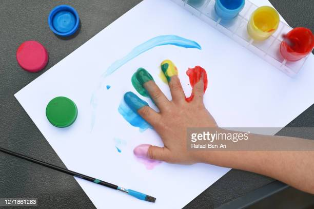 child painting with his hand with many colors on a white paper on a table - rafael ben ari stockfoto's en -beelden