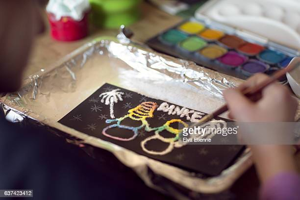 Child painting with watercolours and salt