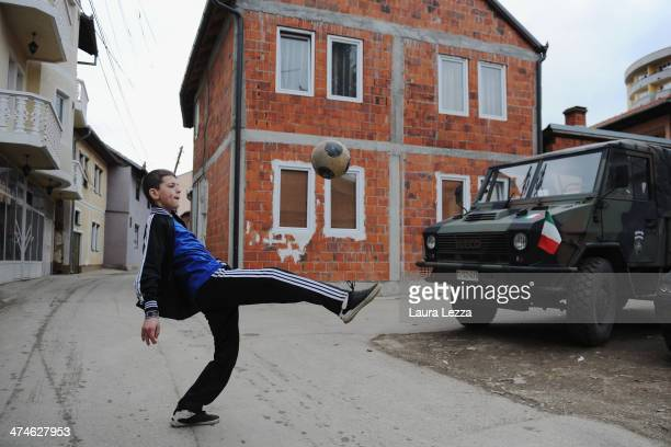 A child paly football near an Italian KFOR vehicle during elections in Mitrovica North to elect the Mayor on February 23 2014 in Mitrovica Kosovo The...