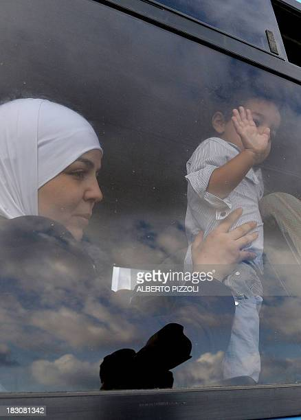 A child part of a group of migrants arrived in Lampedusa few days ago waves from the window of a bus as they arrive in the harbour of Lampedusa to be...