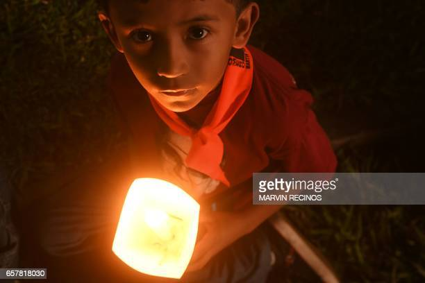 A child participates in the pilgrimage of light during a vigil at the Salvador del Mundo square in San Salvador on March 25 commemorating the 37th...