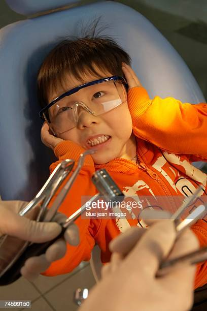 a child patient covers his ears in fear as a dentist displays a variety of dental tools. - dentist horror stockfoto's en -beelden