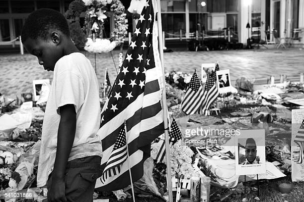 Child pauses at a memorial to victims of the Pulse nightclub shooting on June 17, 2016 in Orlando, Florida. Following a week of sucessive tradgedies...
