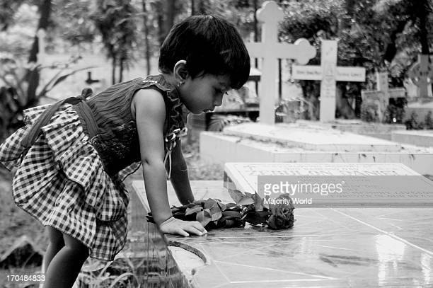 A child pays tribute at her grandfathers grave in the cemetery in Wari in Dhaka Bangladesh June 19 2009
