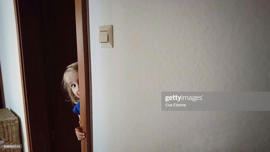 Child peaking around a door frame : Stock Photo