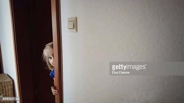 Child peaking around a door frame