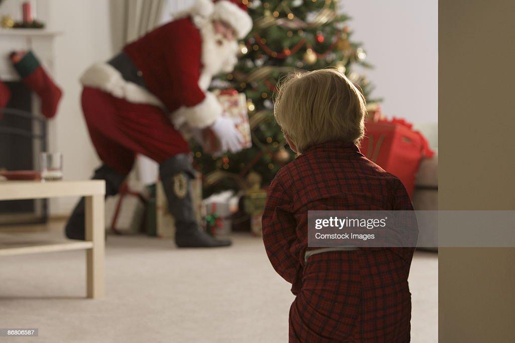 Child peeking at santa claus : Stock Photo
