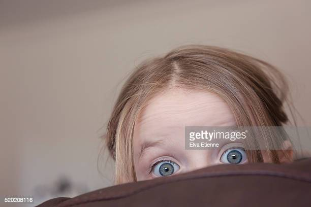 Child peeking out with surprised expression