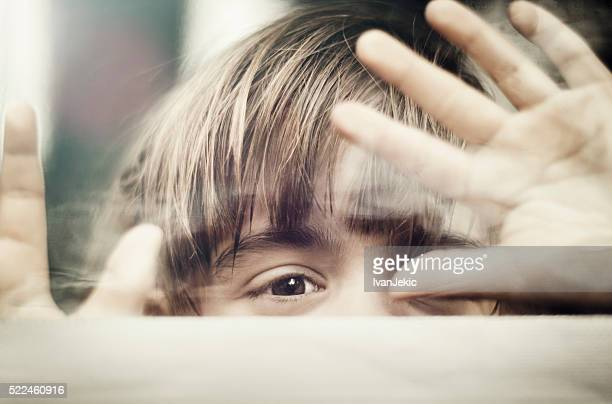 Child peeking through window