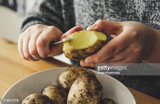 child peeling potatoes - prepared potato stock pictures, royalty-free photos & images