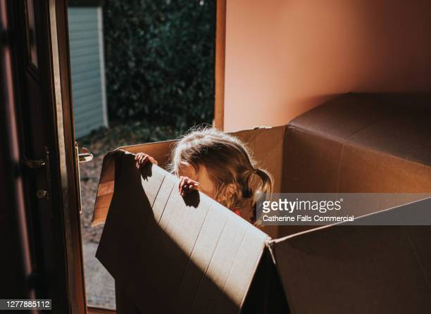 child peers out of a huge cardboard box, which obscures her face. - obscured face stock pictures, royalty-free photos & images