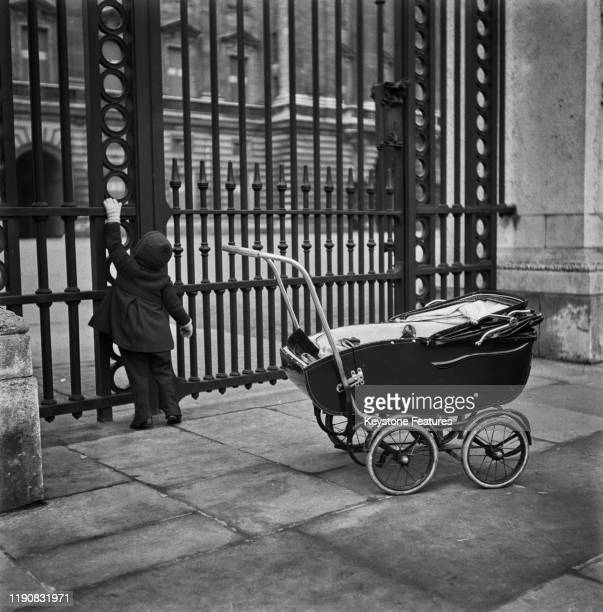A child peers through the gate of Buckingham Palace in London on Investiture Day during World War II April 1941