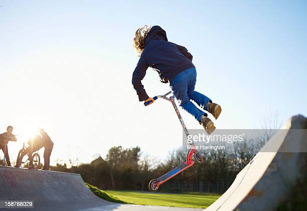 Child performing stunt on scooter at skate park.