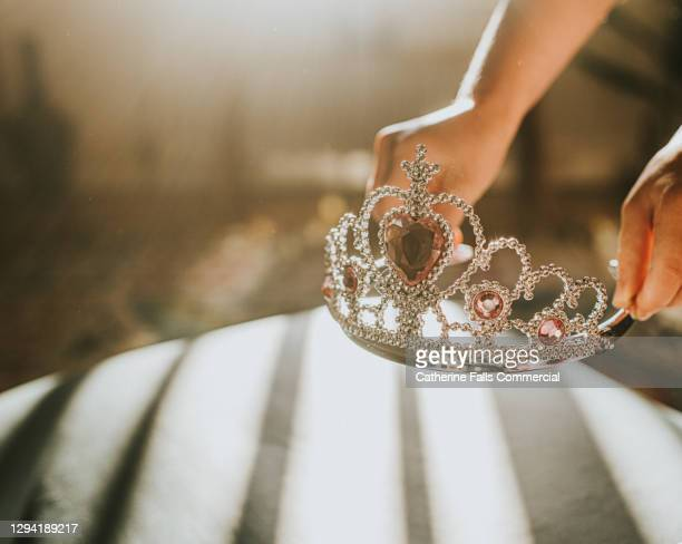 child picking up a plastic jewelled tiara toy in sunlight - royalty stock pictures, royalty-free photos & images