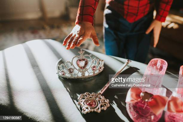 child picking up a plastic jewelled tiara toy in sunlight - queen royal person stock pictures, royalty-free photos & images