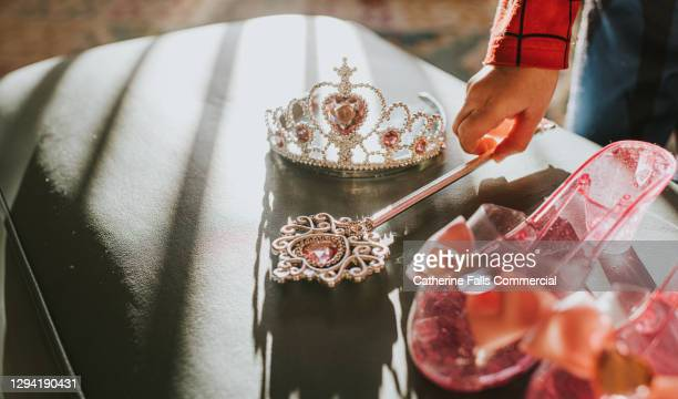 child picking up a plastic jewelled wand in sunlight - silver shoe stock pictures, royalty-free photos & images