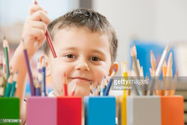 child picking up colored pencil in school classroom - color pencil stock pictures, royalty-free photos & images