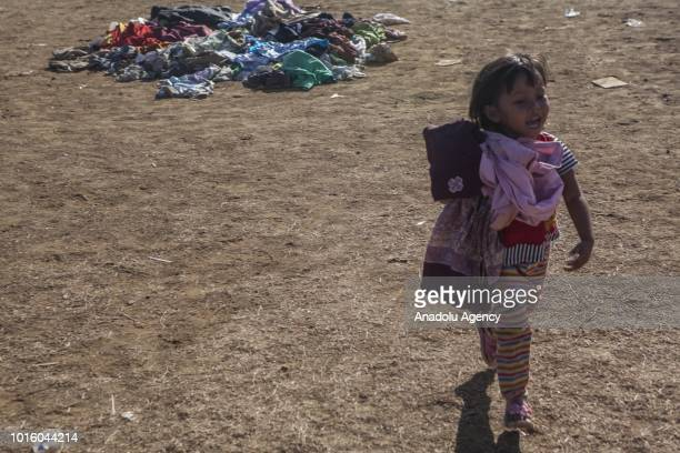 A child picks clothes which are donated for people affected by earthquake at a temporary shelter in Lombok Indonesia on August 13 2018 According data...