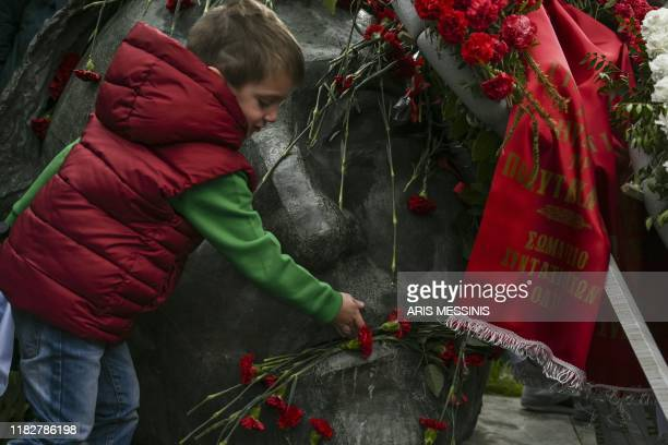 A child place a red carnation on the monument in memory of the victims of the 1973 student's uprising against the USbacked military junta at the...