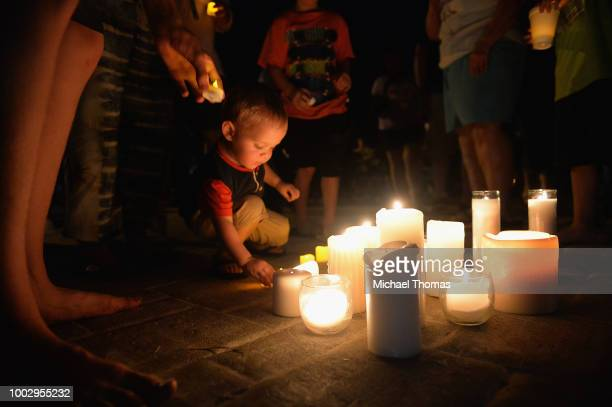 A child places a candle down during a evening candlelight prayer vigil at Life Christian Center Church on July 20 2018 in Branson Missouri Hundreds...