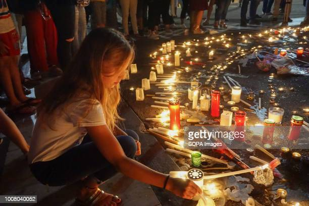 A child places a candle during a silent protest People gathered outside the Hellenic Parliament in memory of the 91 victims of the deadly fire in...