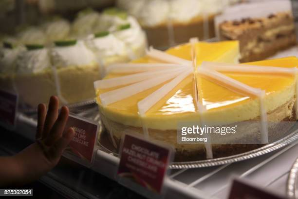 A child places a hand on a display case of flavored cheesecakes at a Cheesecake Factory Inc restaurant in the Canoga Park neighborhood of Los Angeles...