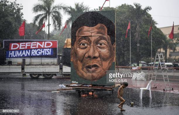 TOPSHOT A child play as it rains during a protest in Manila on December 10 as activists commemorate the International Human Rights Day Philippine...