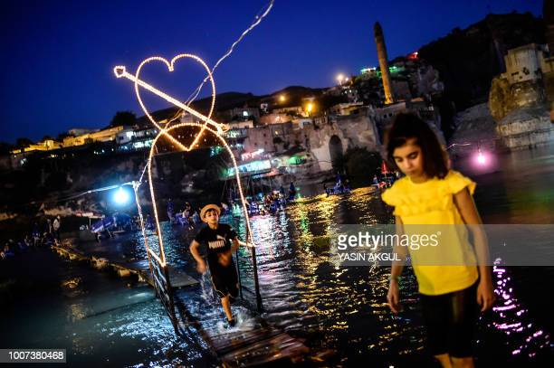TOPSHOT Child play near the along the Tigris River overlooked by the 12000yearold Hasankeyf settlement and ancient citadel town which will soon be...