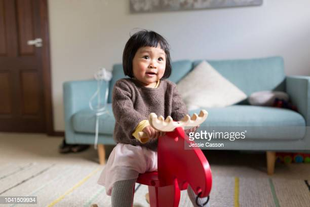 child play riding wooden reindeer - chinese ethnicity stock pictures, royalty-free photos & images
