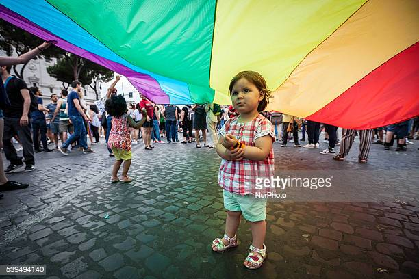 A child play under a giant rainbow flag a symbol of the gay rights movement as she take part in the 22nd annual Gay Pride Parade in Rome Italy on...