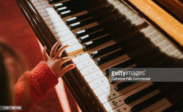 child playing a piano - human finger stock pictures, royalty-free photos & images