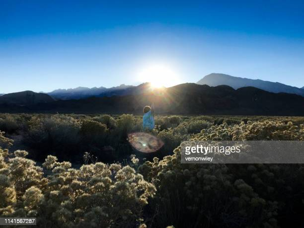Child playing and dancing in the mountains as the sun sets