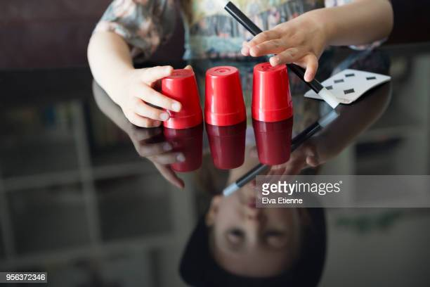 child playing and performing magic trick - goochelaar stockfoto's en -beelden