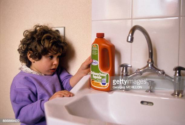 Child playing at risk while handling dangerous product at home on March 25 1990 in France