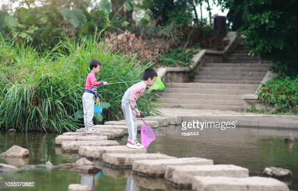 kind spielt mit einem fischen - süßwasser stock-fotos und bilder