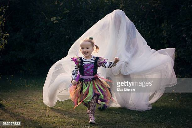 child (3-4) playing game in halloween costume - ghost player foto e immagini stock