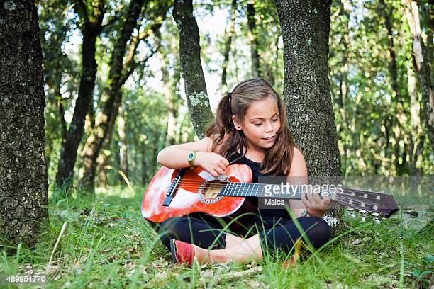 Child playing guitar in a forest