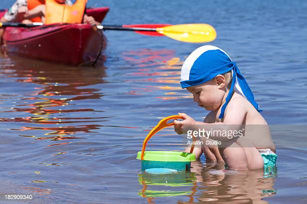 Child playing in the water flowing in the background kayak.