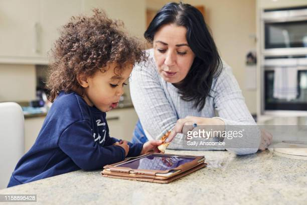 child playing on a digital tablet - reading stock pictures, royalty-free photos & images