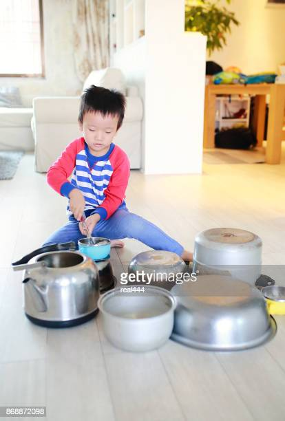 Child playing on floor with pots and pans