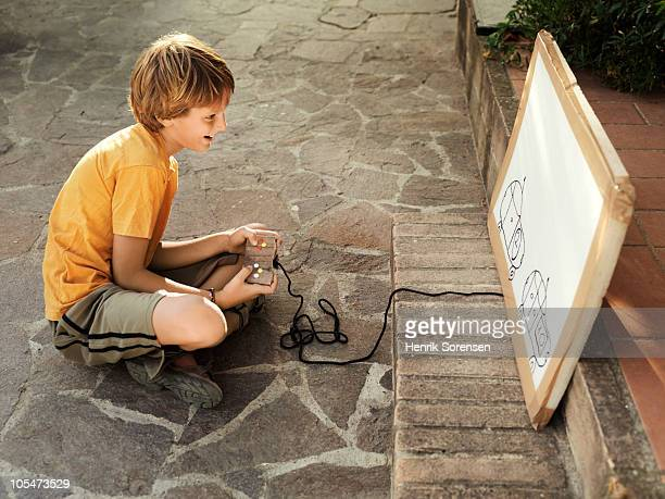 Child playing on homemade computer game in garden