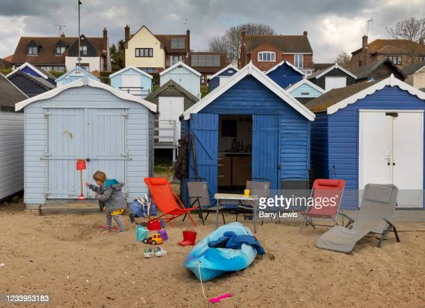 Child playing on the beach by the beach huts on a small island with sandy beaches on the river Blackwater on 2nd May 2021 in Mersea Island, Essex,...