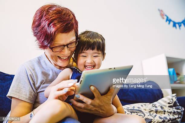Child playing tablet with her grandma joyfully