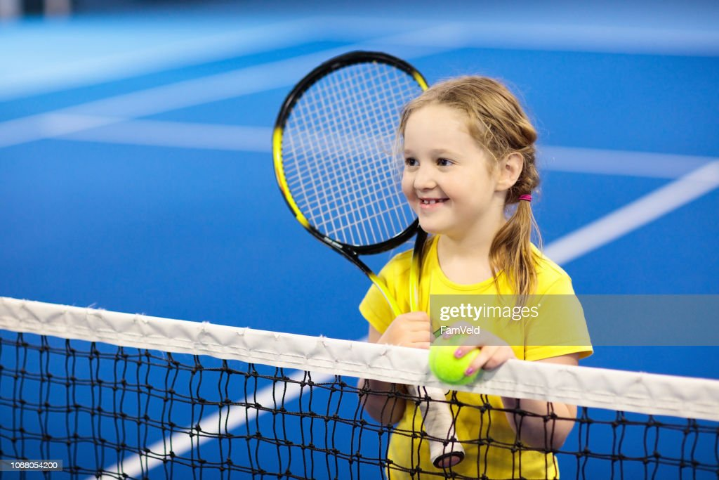Child playing tennis on indoor court : Stock Photo