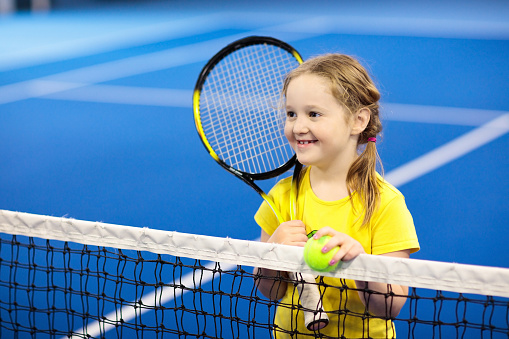 Child playing tennis on indoor court 1068054200