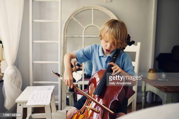 child playing the cello - childhood stock pictures, royalty-free photos & images
